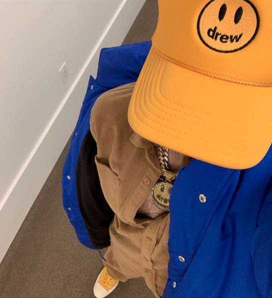 Justin Bieber shows off a hat from his clothing line.