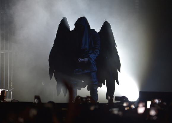 R Kelly on stage with black demon wings in 2016