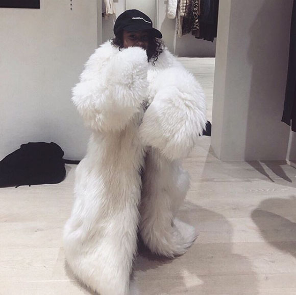 North West wearing a faux fur coat.