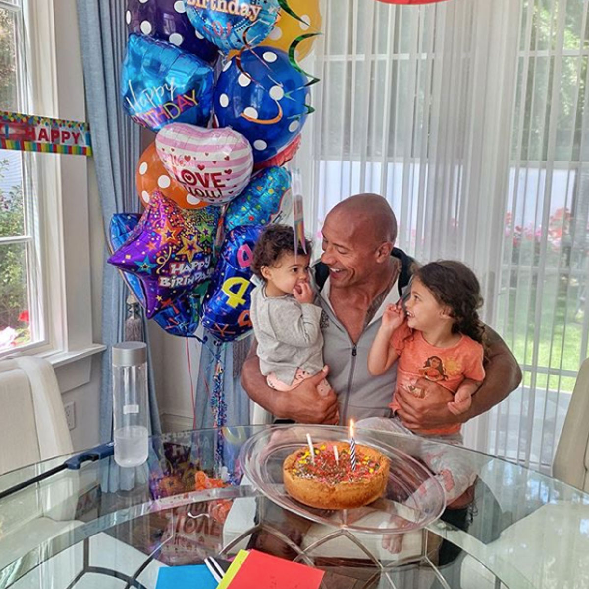 Dwayne Johnson posing with two of his three daughters